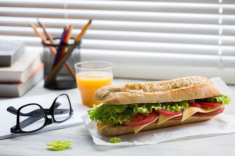 Sandwich et verre de jus d'orange posé sur un bureau